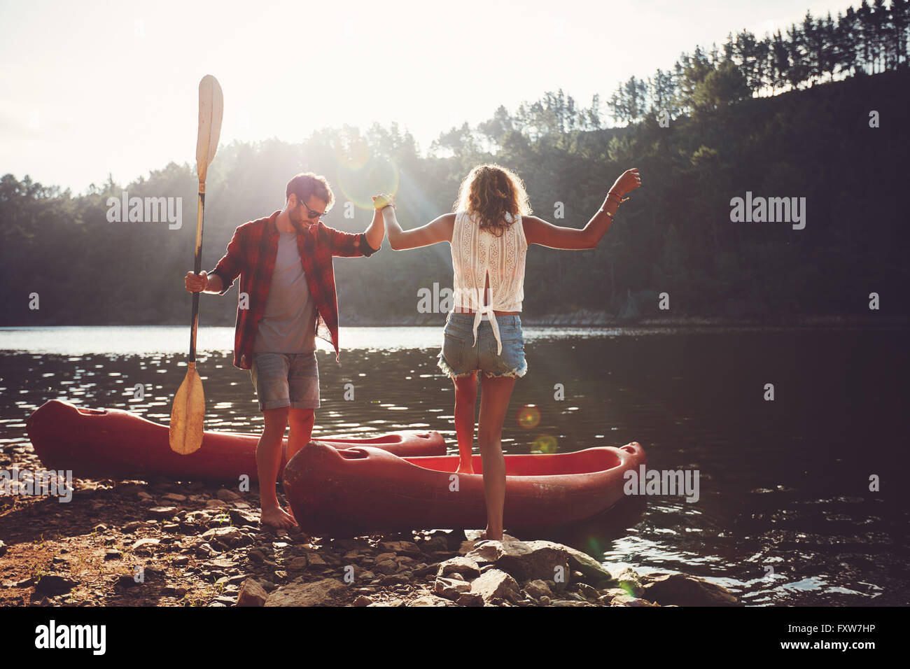 Young man helping woman to step into the kayak. Couple going for a canoe ride in the lake. - Stock Image