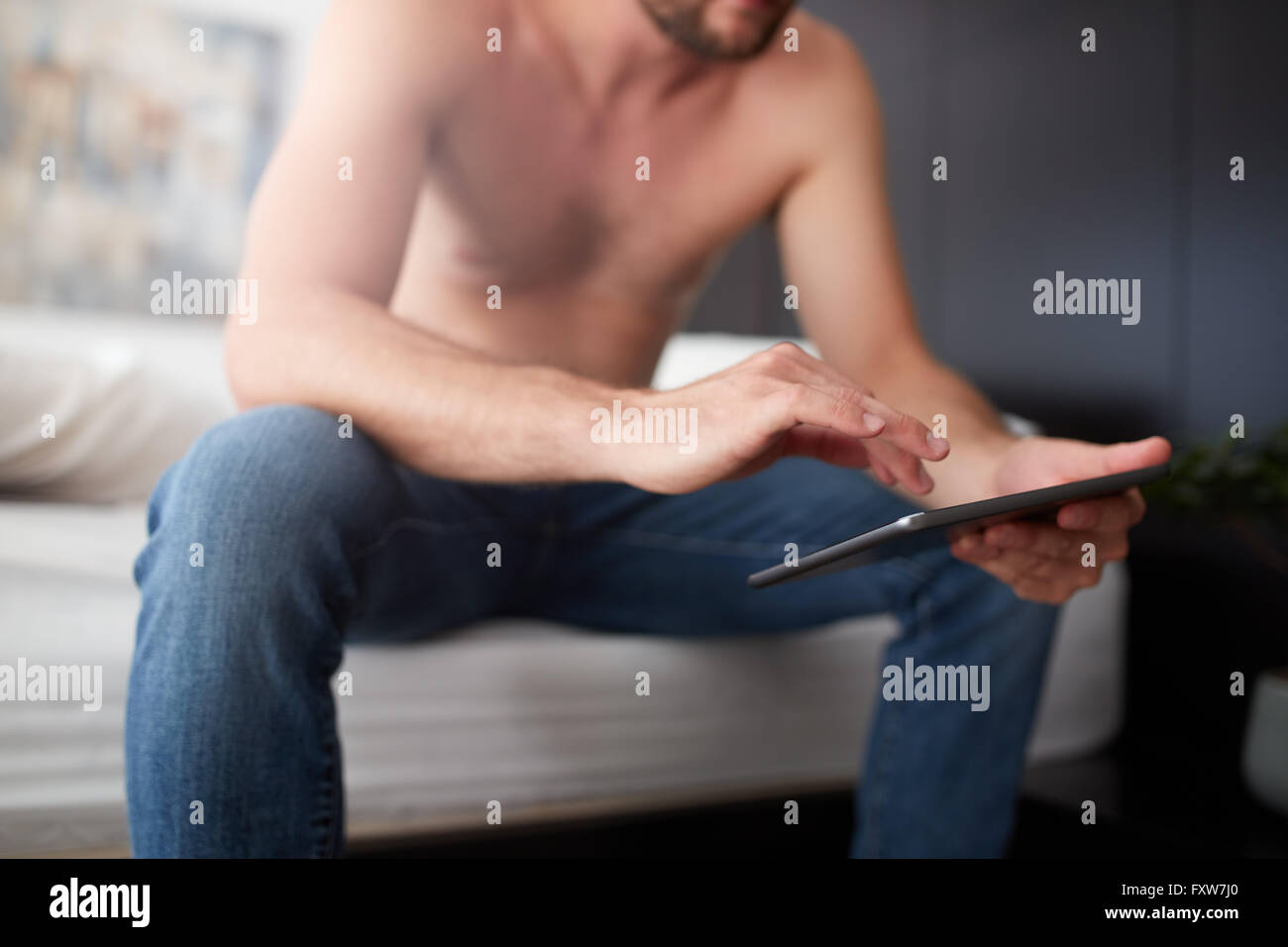 Close up portrait of young man sitting on the bed using digital tablet. Focus on hands and touch screen computer. - Stock Image