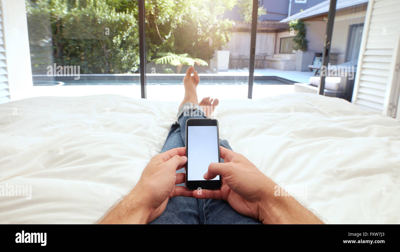 Closeup image of human hand holding mobile phone with blank screen on bed. POV shot of man lying on bed using smart - Stock Image