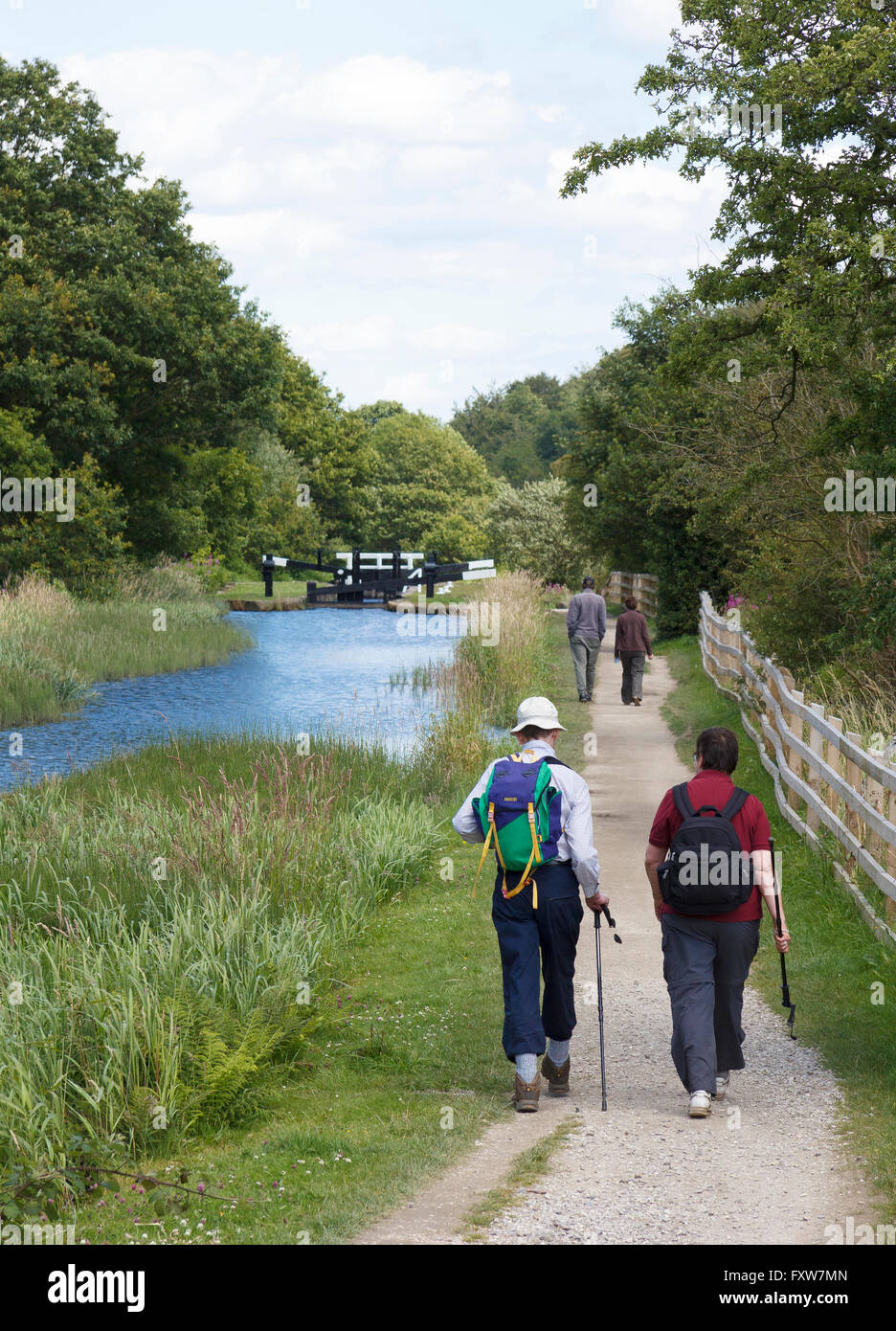 People walking along the towpath of the Huddersfield Narrow Canal in the Colne Valley, West Yorkshire, UK - Stock Image