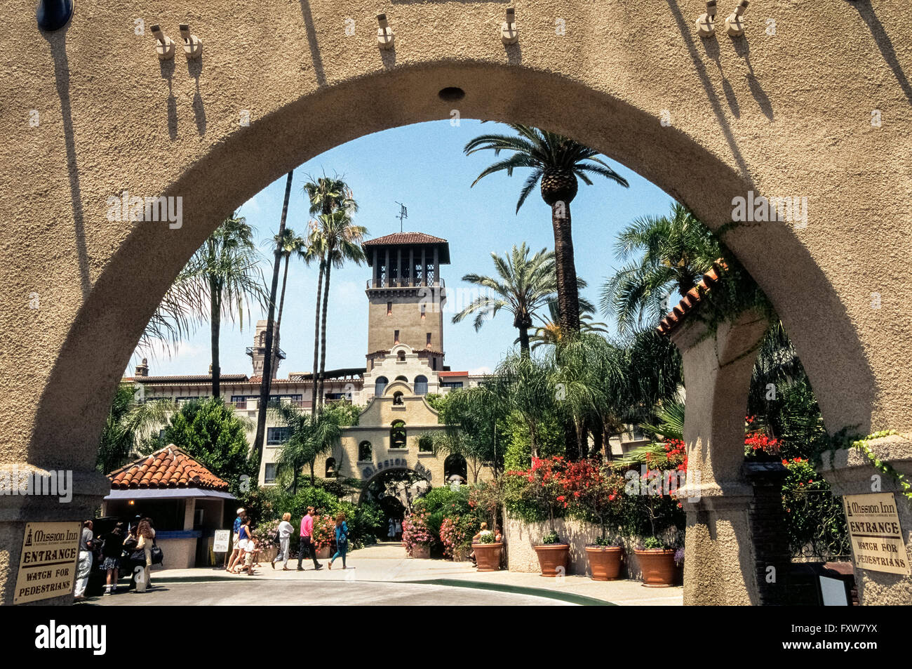 Hotel guests and visitors head to the entrance of the historic Mission Inn that has long attracted U.S. Presidents, - Stock Image