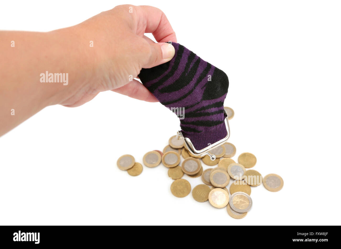 A woman empties her sock which is filled with money - Stock Image