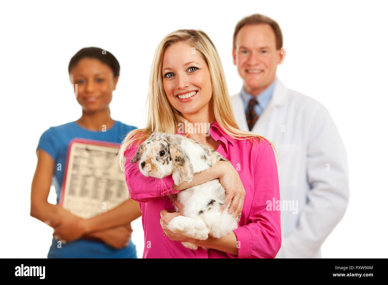 Series with a Cacucasian Veterinarian, and mixed-ethnicity group of assistants and customers.  Holding rabbit, cat - Stock Image