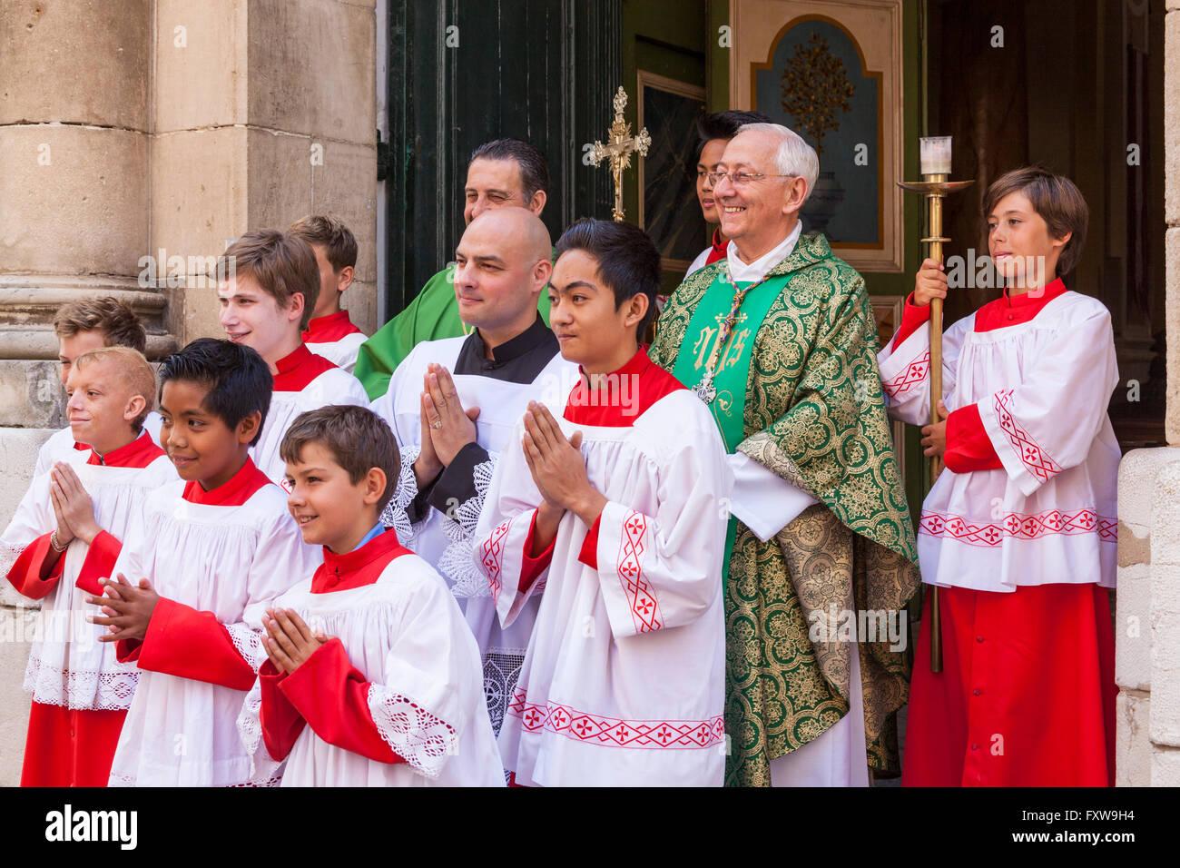 Choir boys and priest outside Notre Dame de L'Assomption Church, Saint Tropez, France - Stock Image