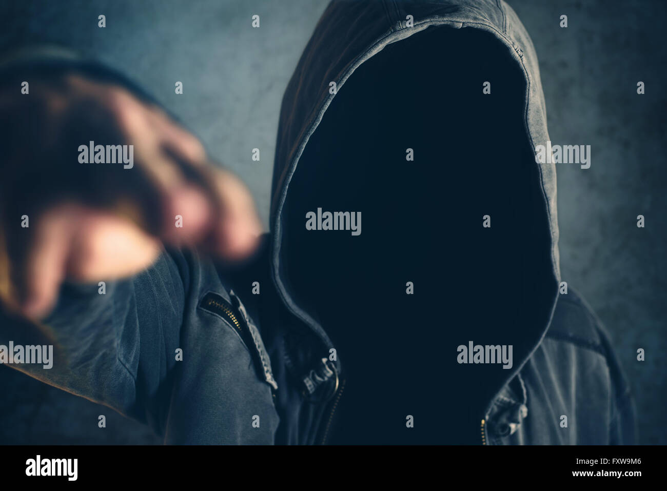 Hooded criminal gesturing gun shooting with fingers, spooky gangster person pointing fingers at viewer, selective - Stock Image