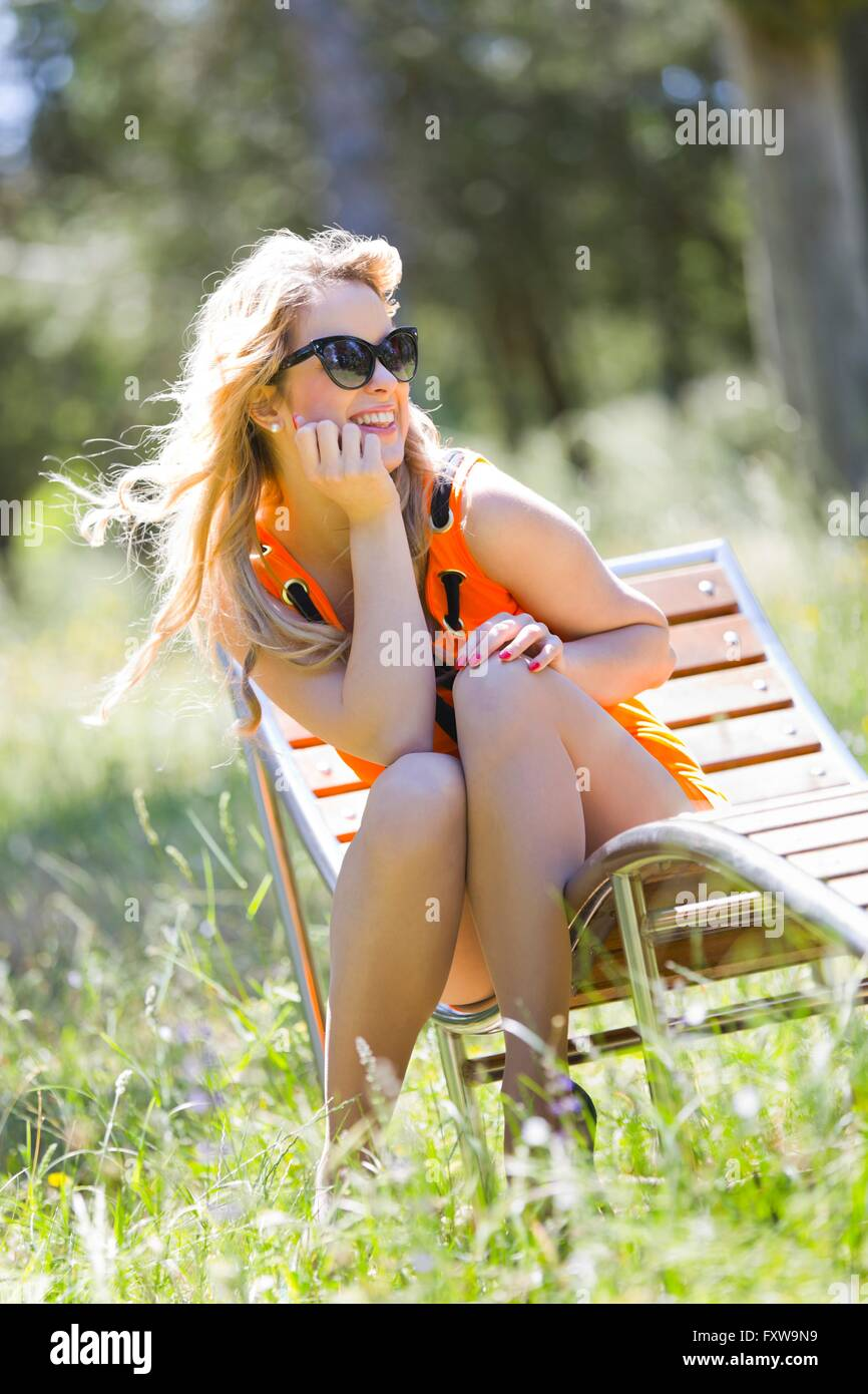 Young woman Spring sunbathe in park outdoors sitting sit looking away happy MR leg in on at near but blondhair Stock Photo