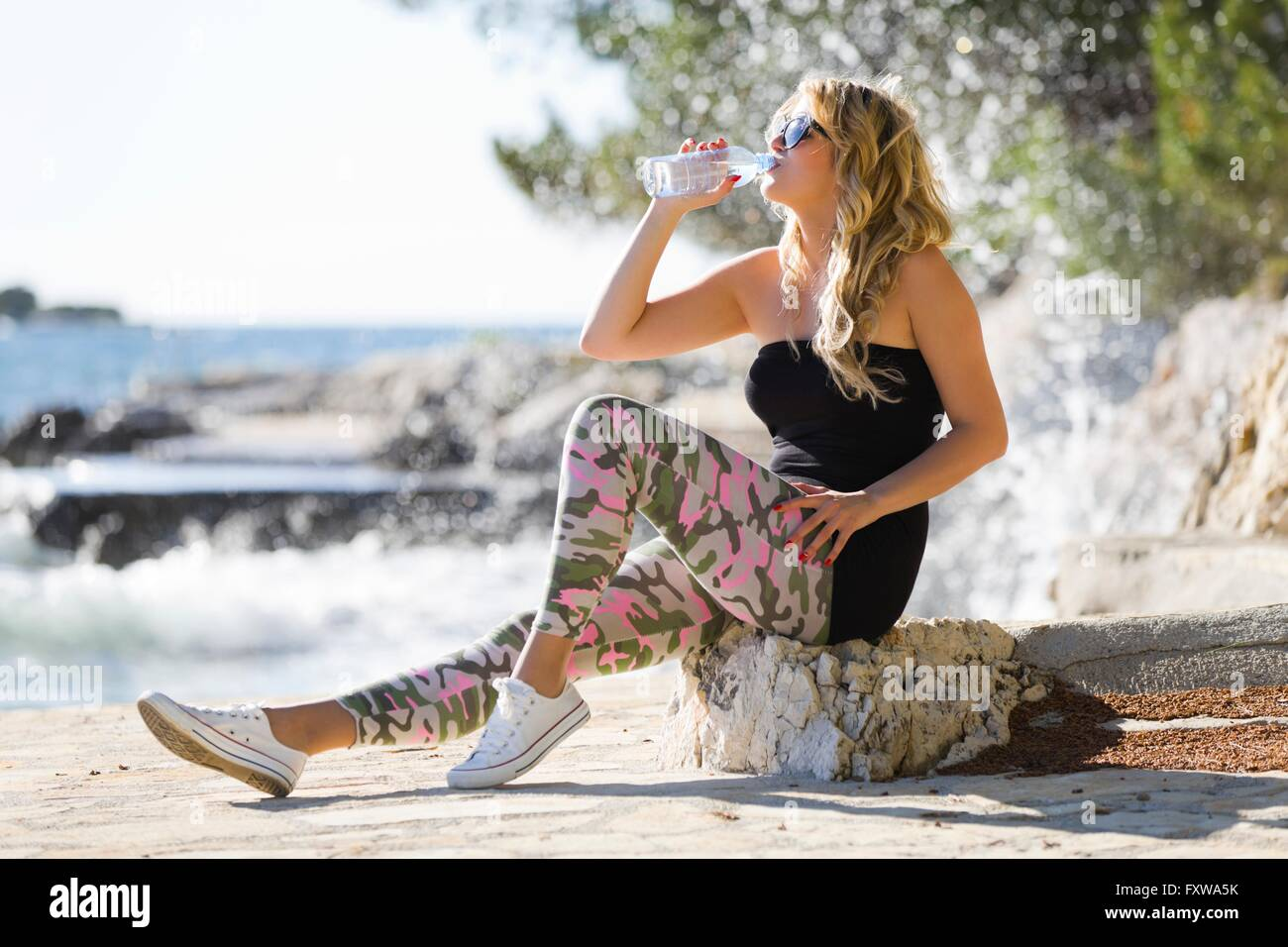 Drinking water young woman seaside army pants sneakers sort curly blonde blond hair sea water thirsty thirst outdoors Stock Photo