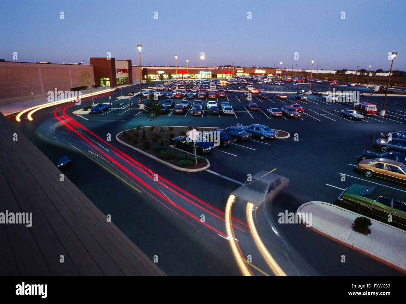 Aerial view of large strip shopping mall and parking lot at dusk; central New Jersey; USA - Stock Image