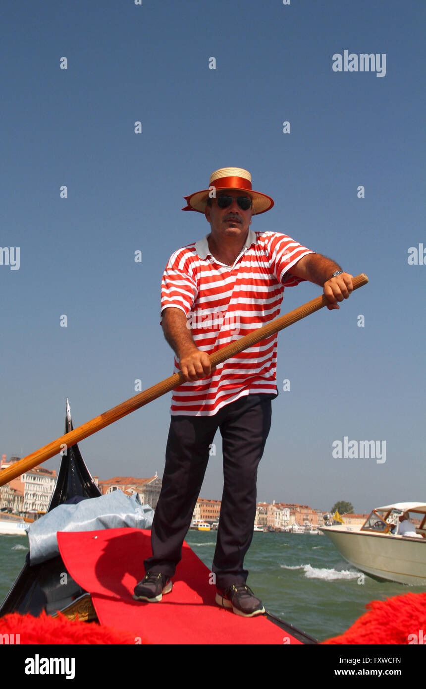 GONDOLIER IN RED HOOPS GRAND CANAL VENICE ITALY 04 August 2014 - Stock Image