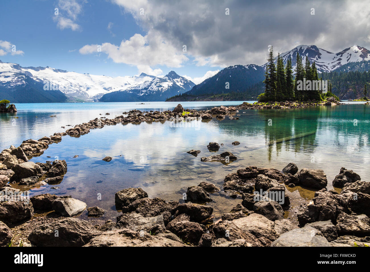 Tranquil, clear waters of Garibaldi lake reflect trees and mountains in shades of blue, emerald and bottle and green - Stock Image