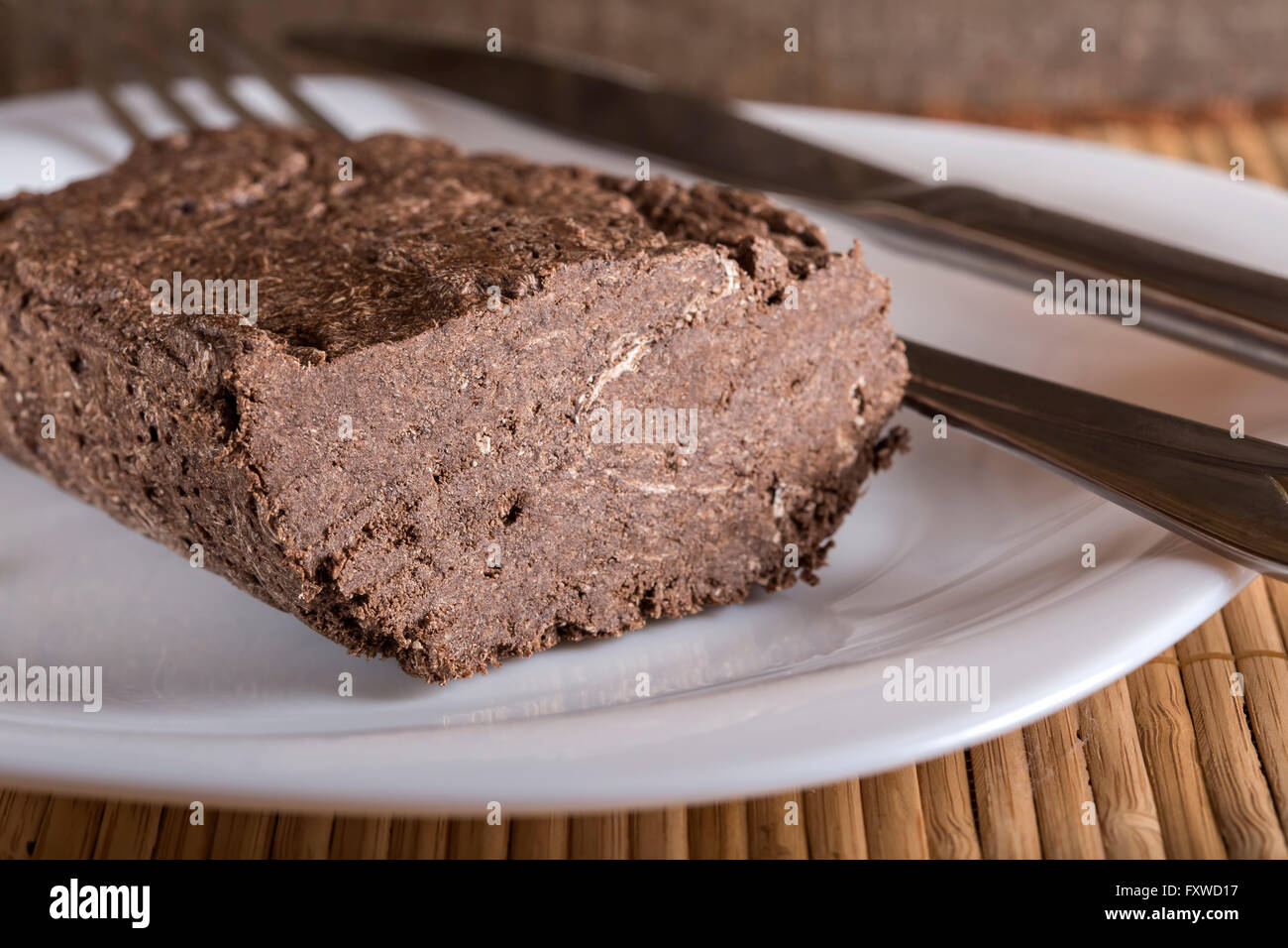 Sunflower halva with cocoa on plate, on wooden background - Stock Image