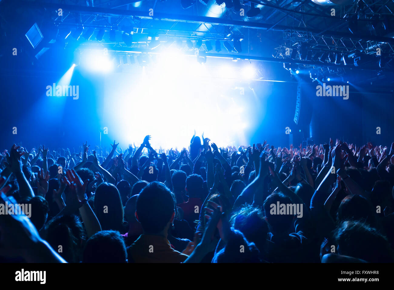 crowd silhouettes at music concert  in front of stage - Stock Image