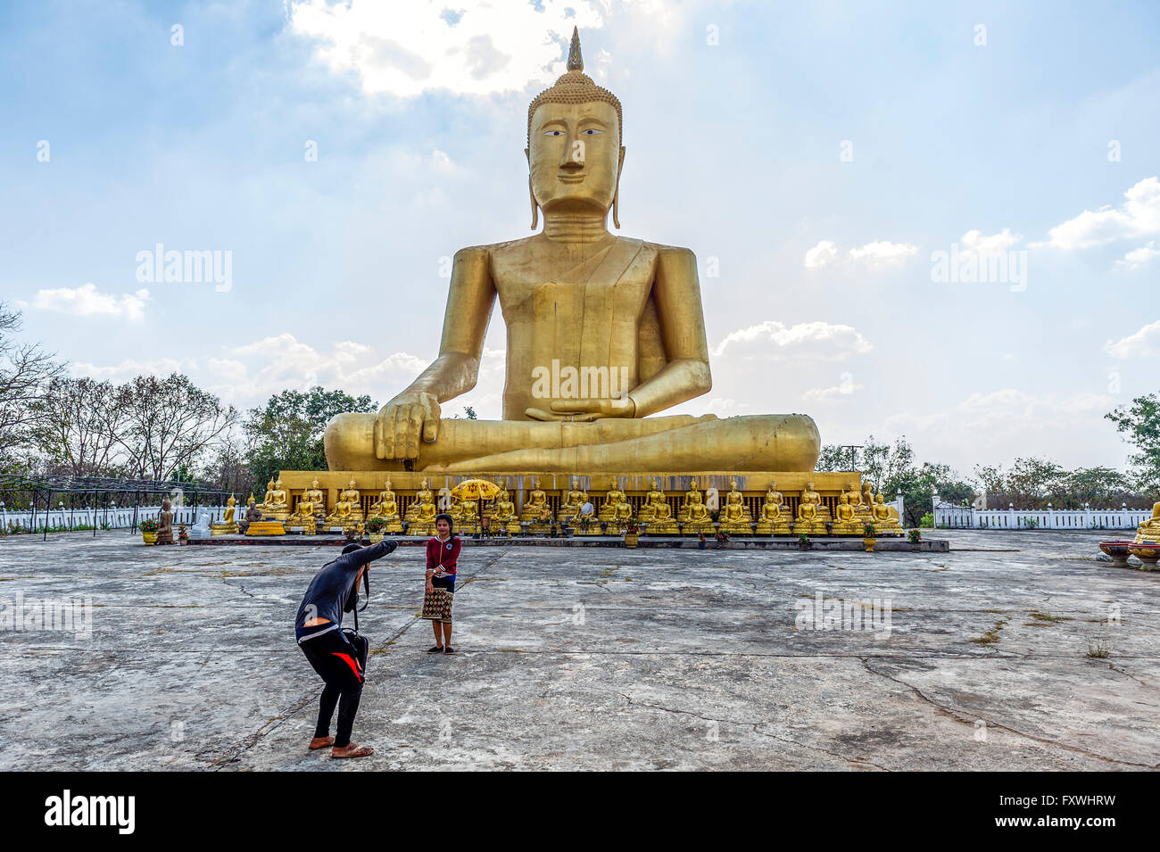 Asia. South-East Asia. Laos. Pakse. Young Lao woman being photographed front of o big Buddha statue. - Stock Image