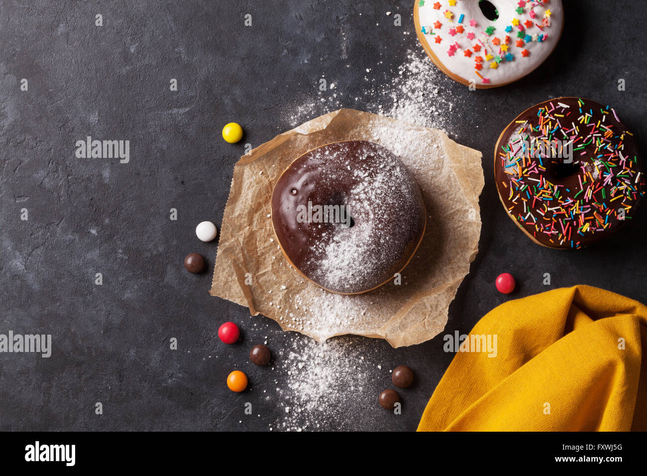 Colorful donuts on stone table. Top view with copy space - Stock Image