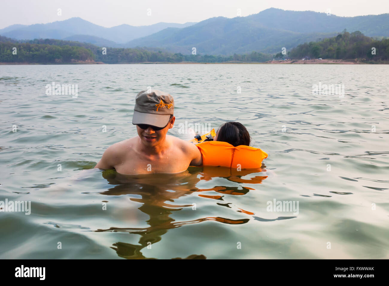 Phayao, Thailand - April 15, 2016. Man at river help women drowning due to water accidents by wearing a life jacket - Stock Image