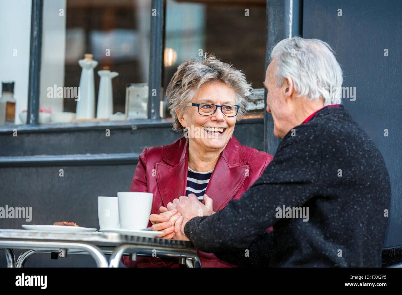 Romantic senior couple holding hands at sidewalk cafe - Stock Image