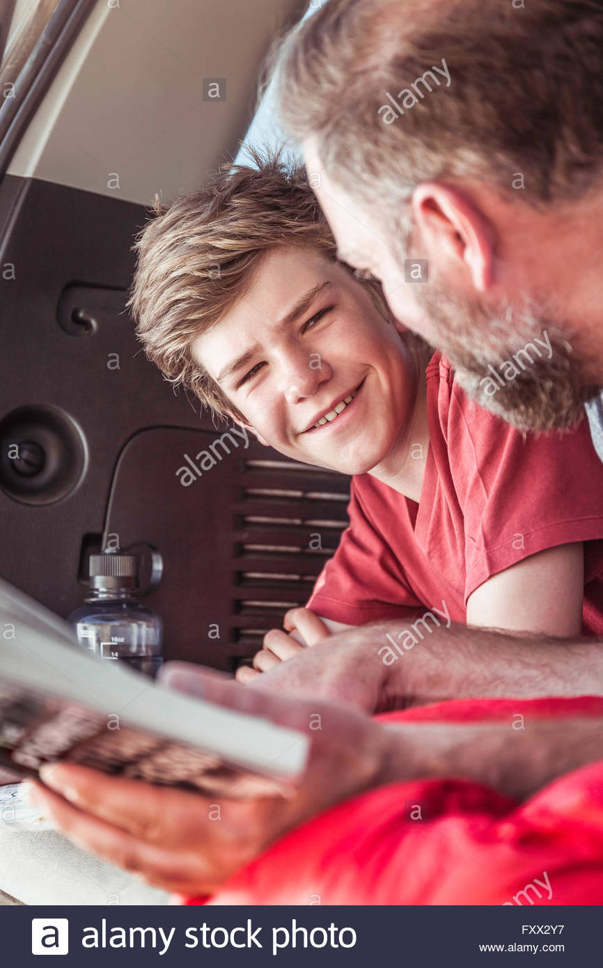 Mature man and teenage son reading guide book whilst lying in vehicle - Stock Image