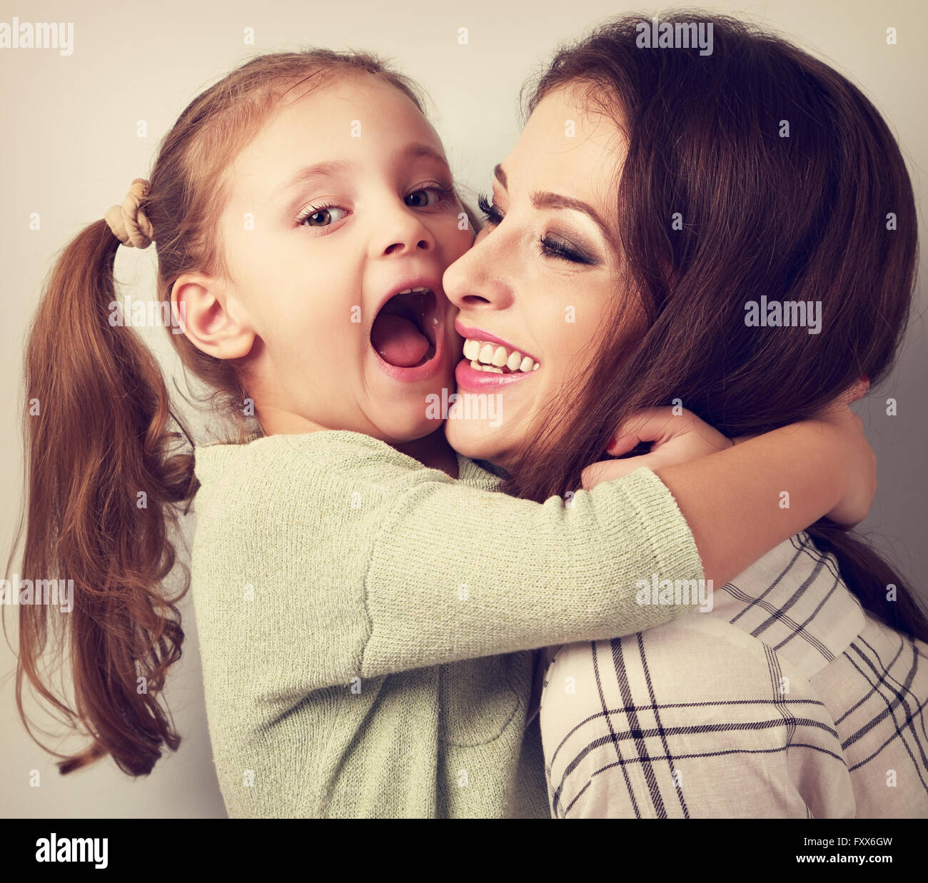Happy grimacing kid wanting to biting her laughing mother in nose with fun face. Vintage toned portrait - Stock Image