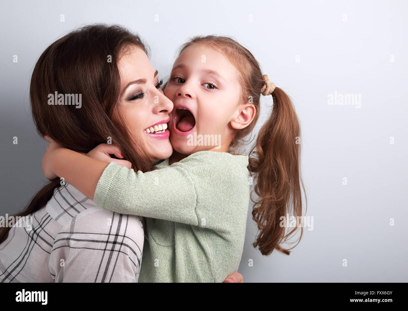 Happy grimacing kid wanting to biting her laughing mother in nose with fun face on blue background - Stock Image