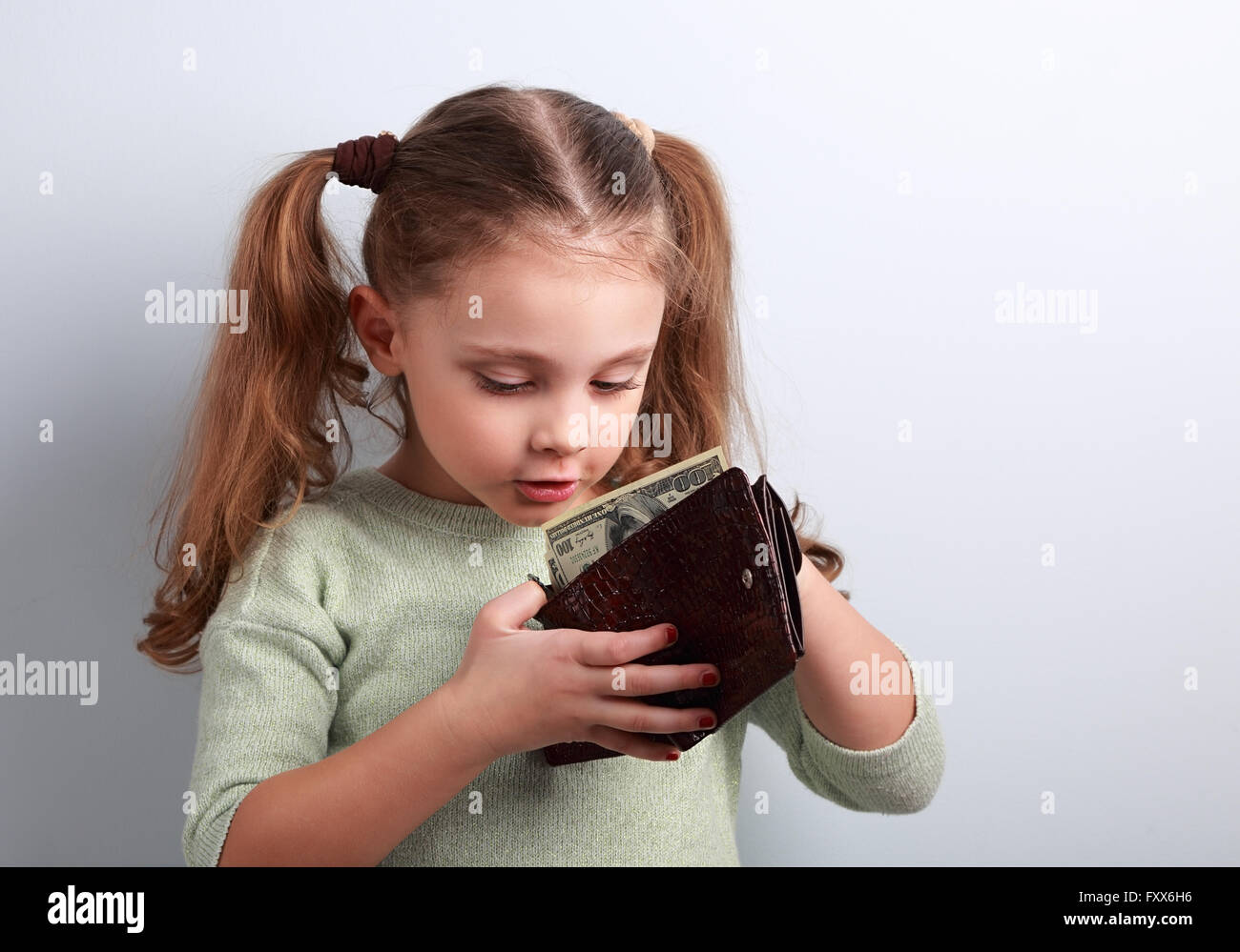 Cute surprising small kid girl looking in mother wallet and want to take money with empty copy space - Stock Image
