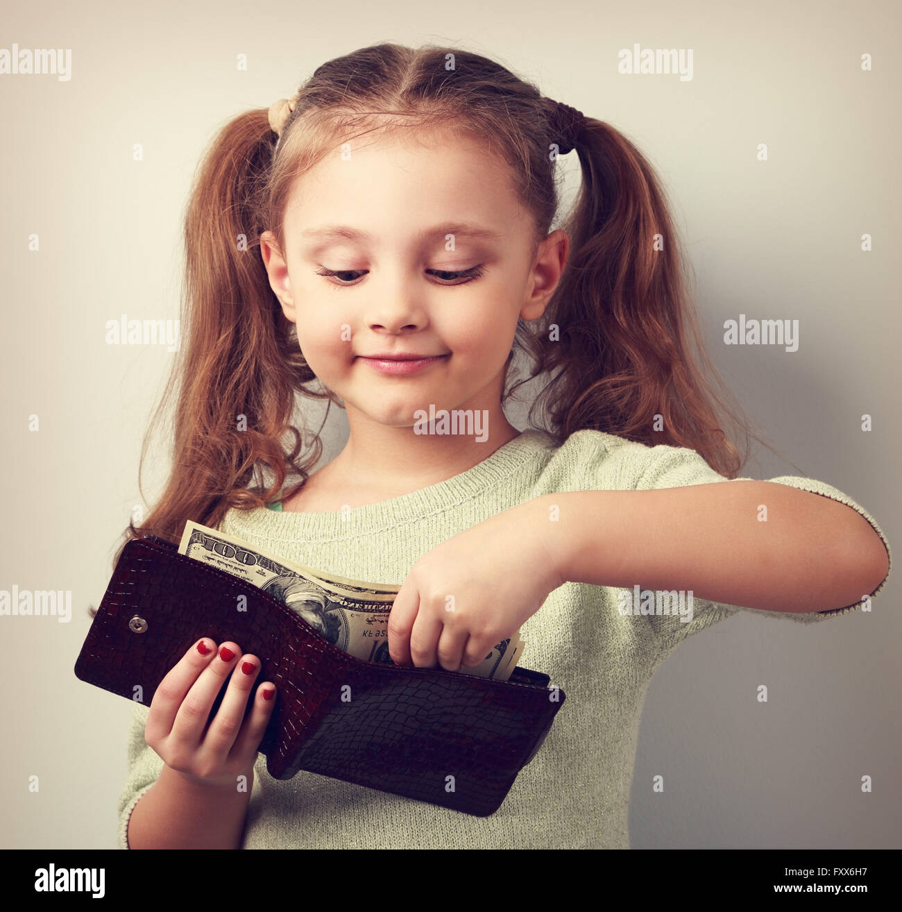 Cute small kid girl taking dollars from mother wallet and looking happy. Toned closeup portrait - Stock Image