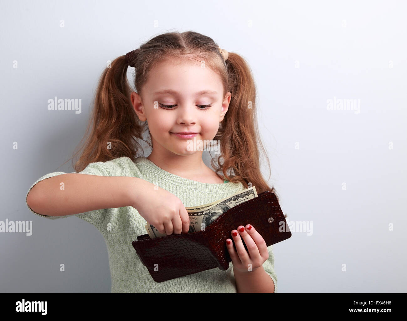 Cute small kid girl taking dollars from mother wallet and looking happy on blue background Stock Photo