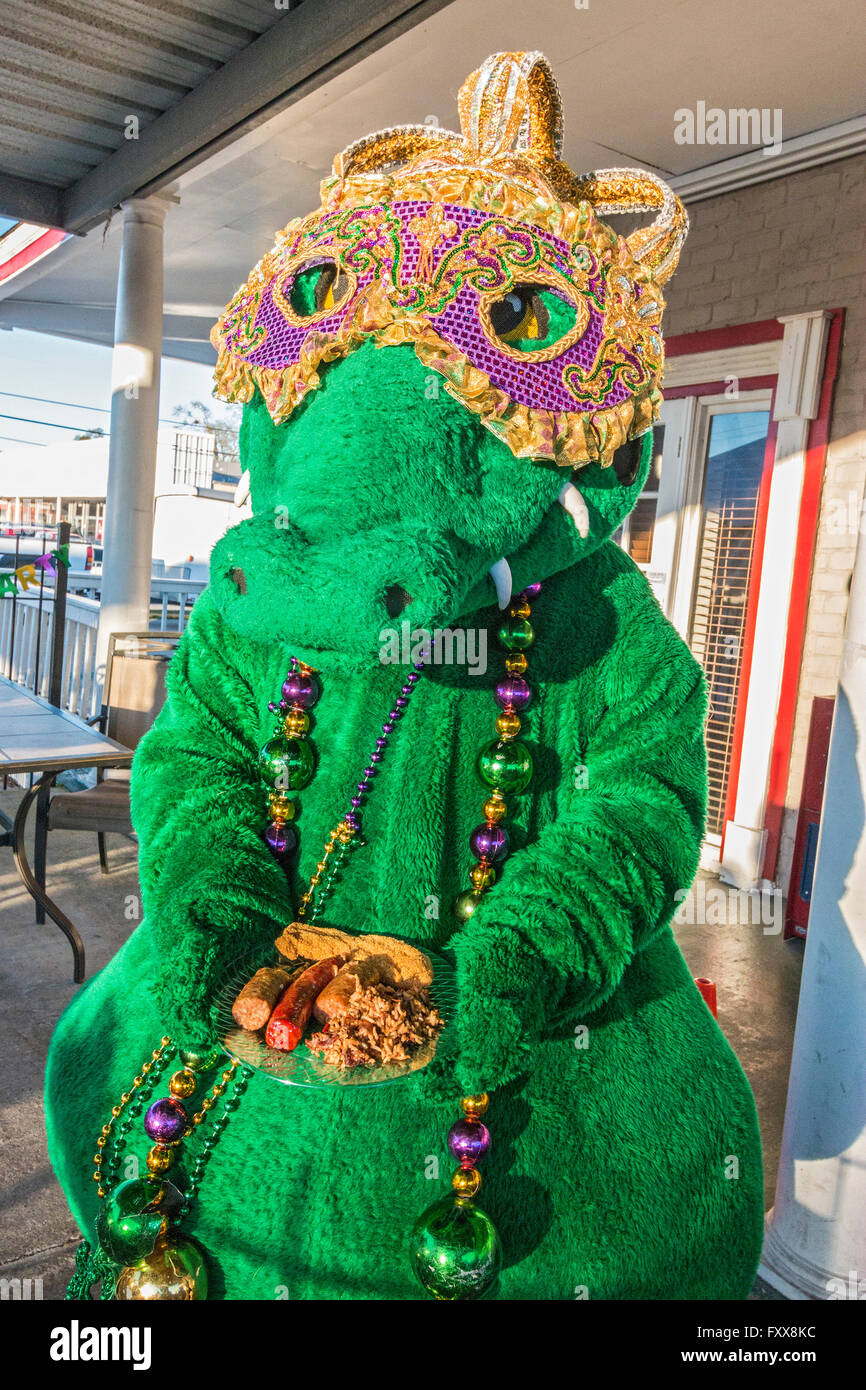 Gumbeaux Gator, the mascot and good will ambassador of Southwest Louisiana holds a plate of Cajun food with fried - Stock Image