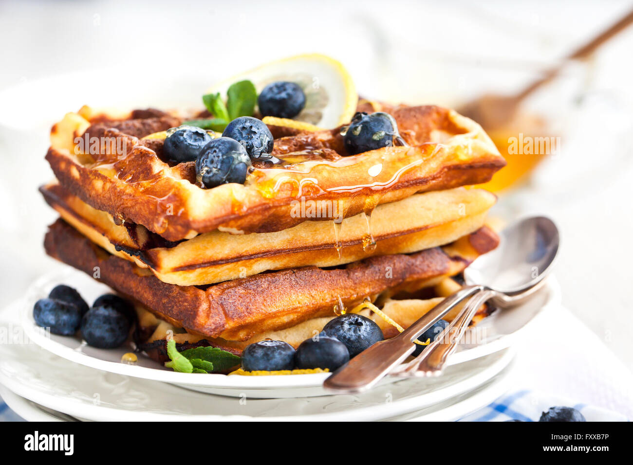 Lemon blueberry waffles with honey, zest, fresh berries and cup of tea - Stock Image