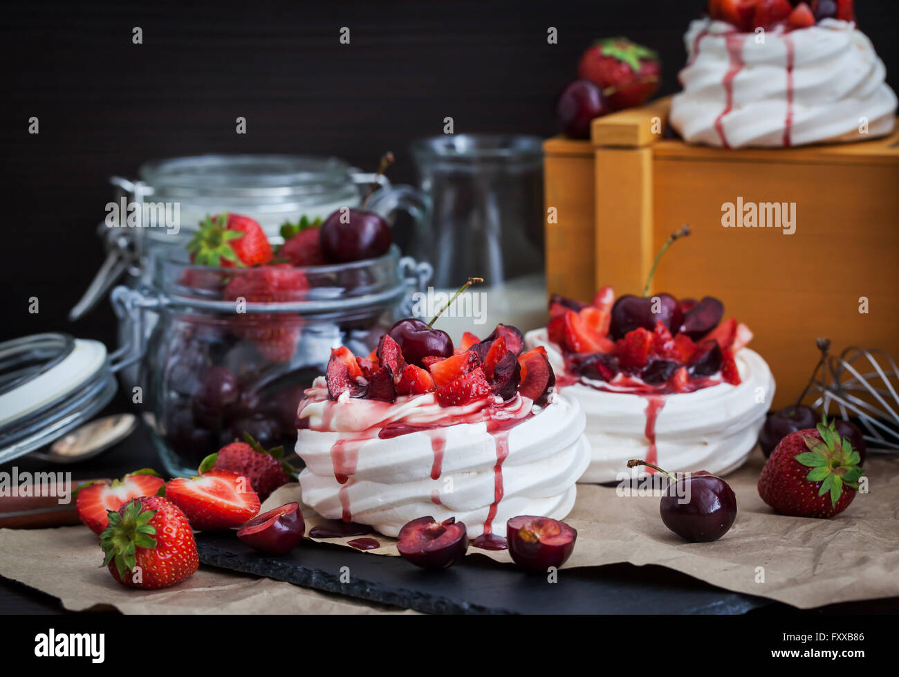 Portion of mini Pavlova meringue cake decorated with fresh strawberry and cherry - Stock Image