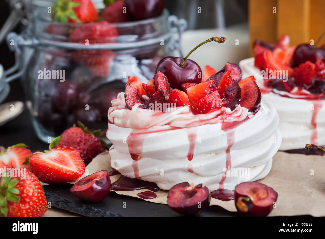 Portion of mini Pavlova meringue cake decorated with fresh strawberry and cherry - Stock Image