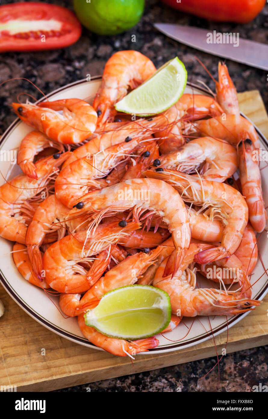 Fresh delicious prawns with lime on the plate - Stock Image