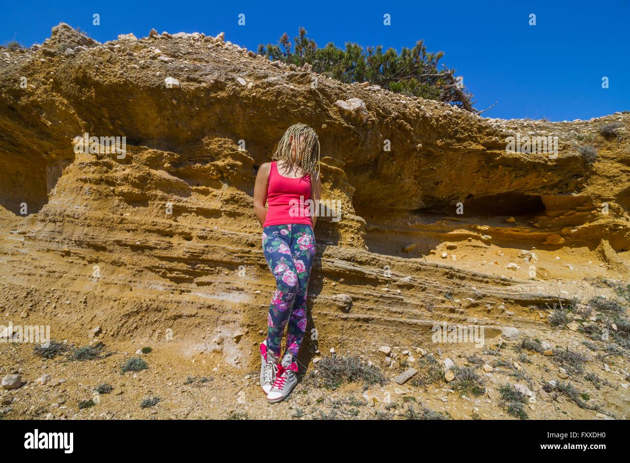 Young woman before earth terrain braided hair hidden eyes face sneakers colorful pants attractive beautiful body Stock Photo