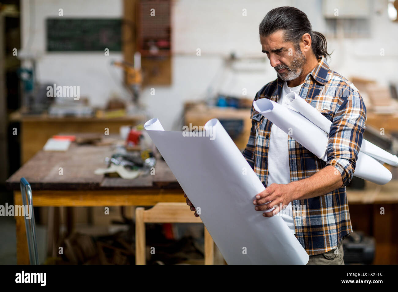 Carpenter looking at a blueprint - Stock Image