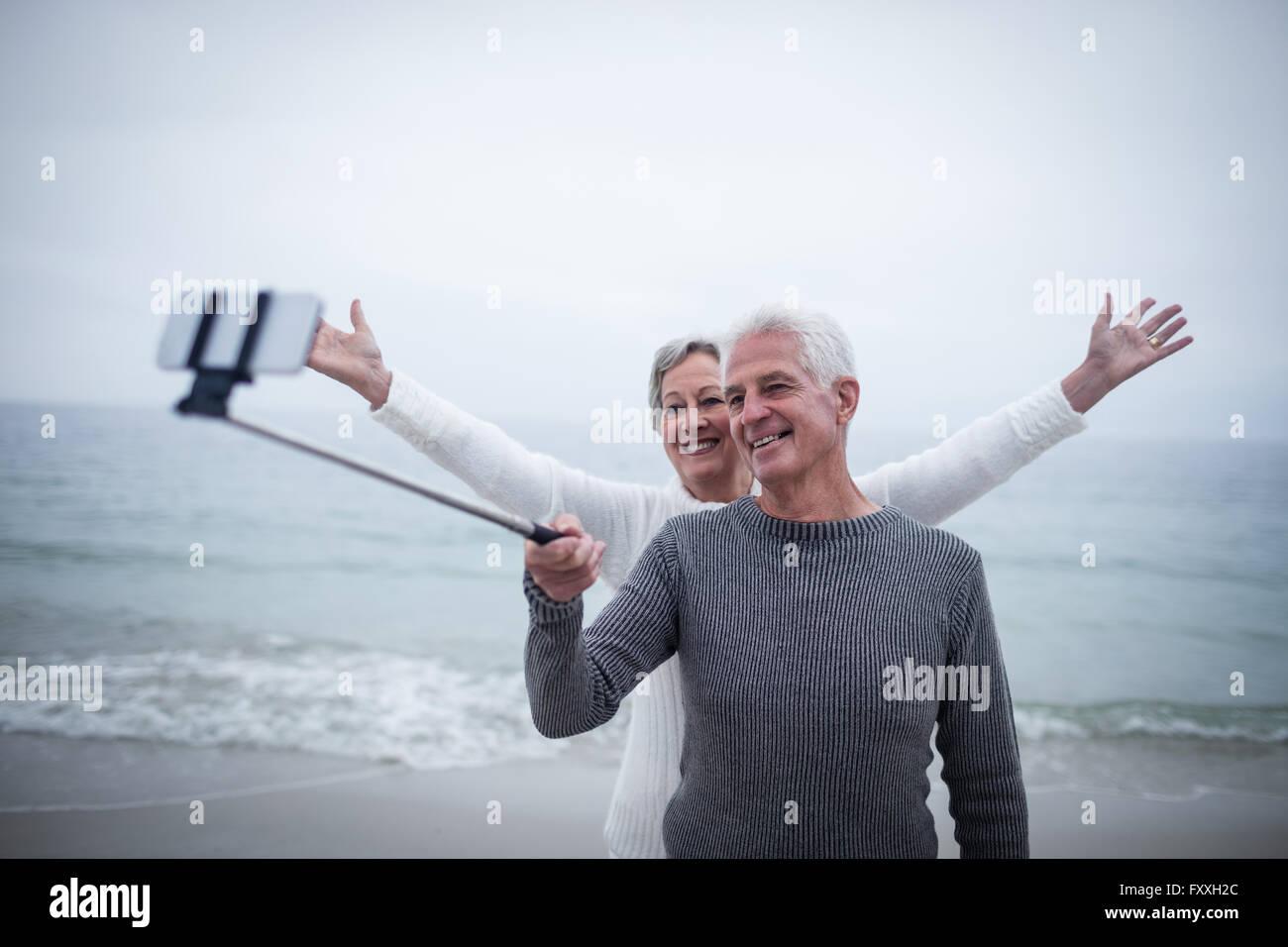 Senior couple taking a selfie on the beach - Stock Image