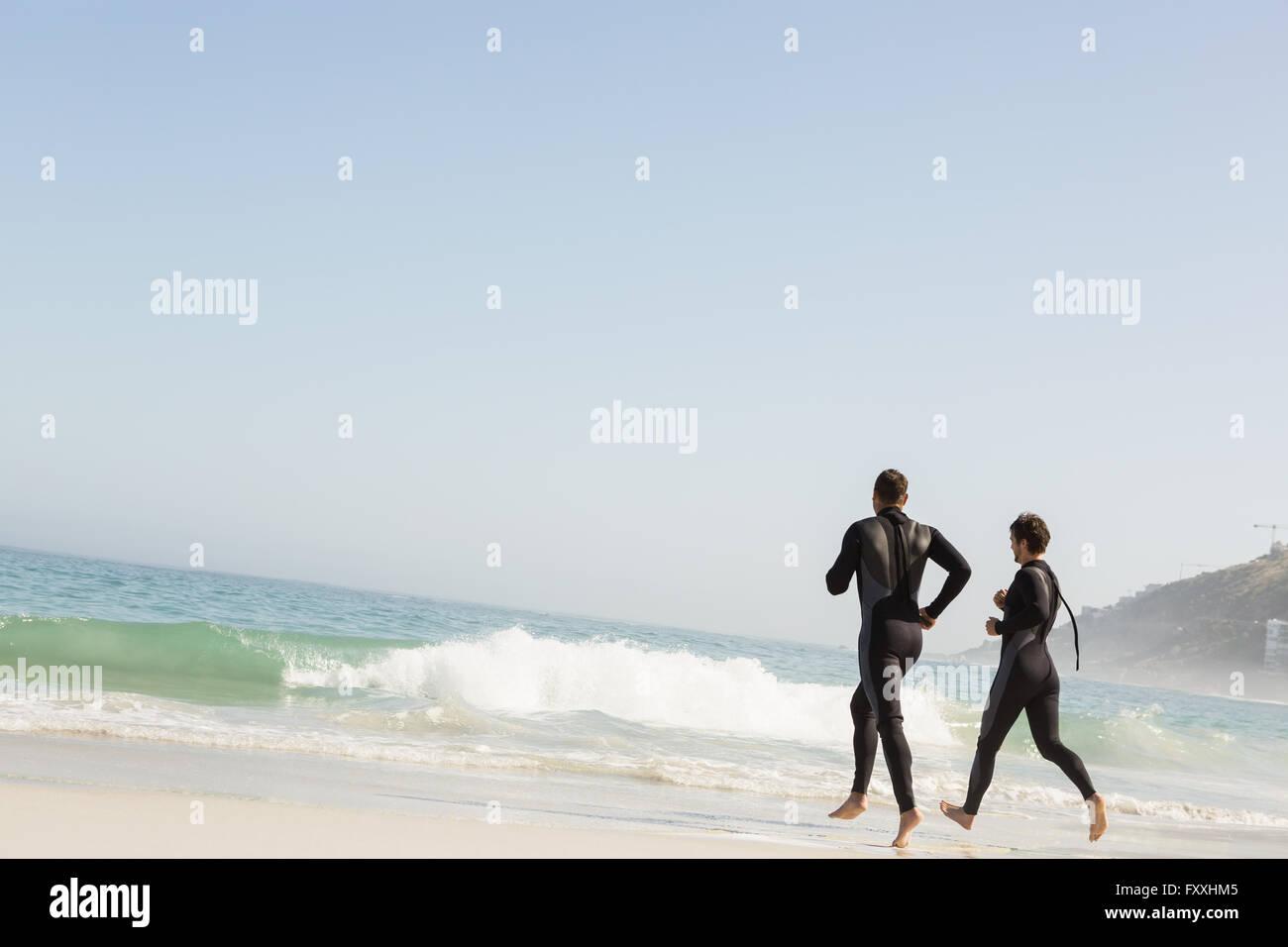 Handsome men running in wetsuits - Stock Image