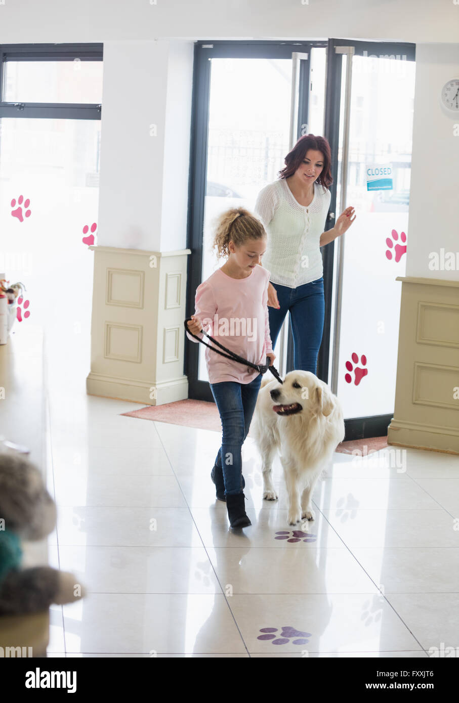 Mother and daughter with dog visiting clinic - Stock Image