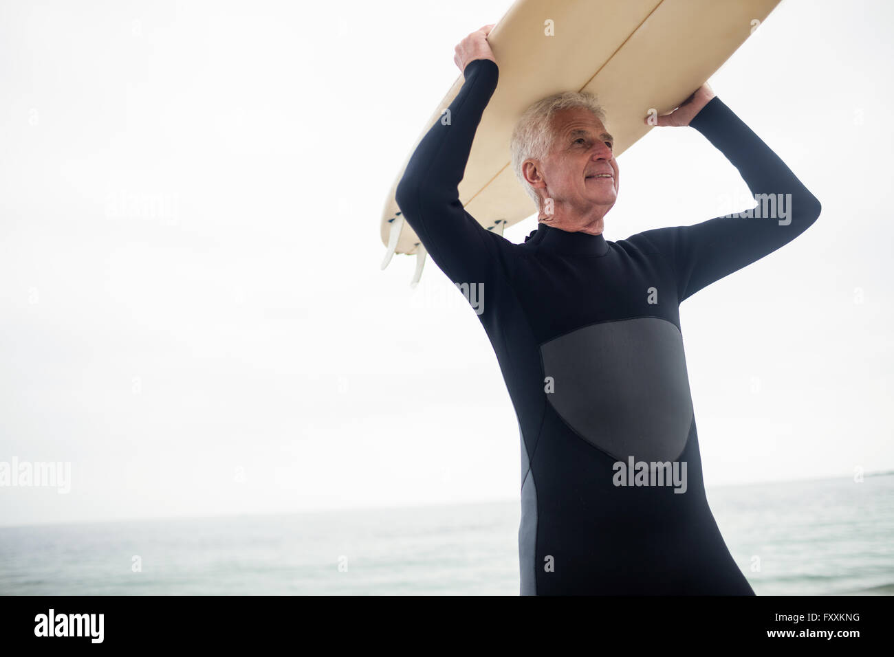 Senior man holding a surfboard over his head Stock Photo