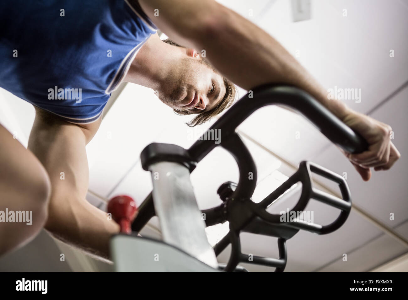 Man working out on exercise bike at spinning class - Stock Image