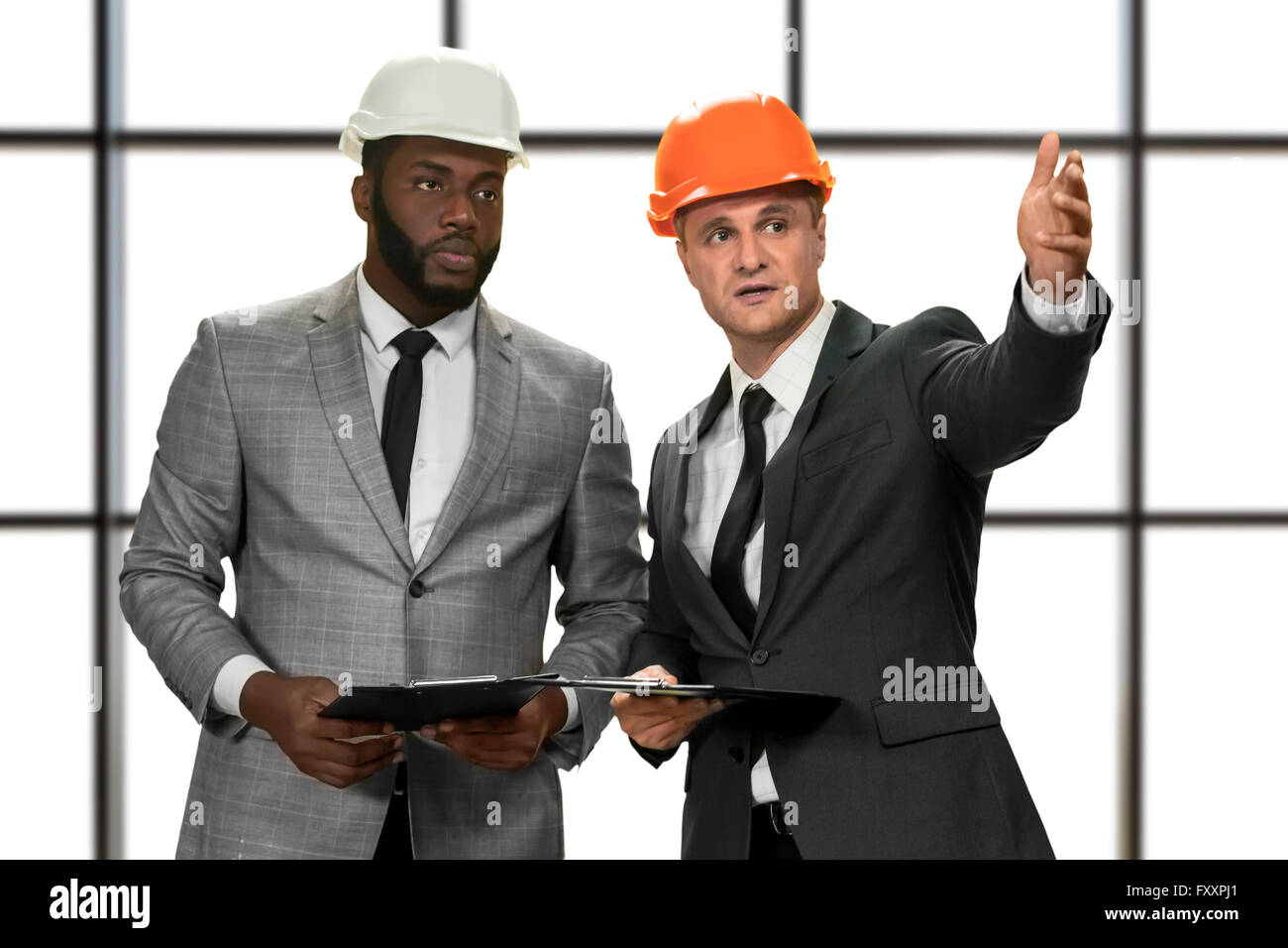 Businessmen wearing construction hats. - Stock Image
