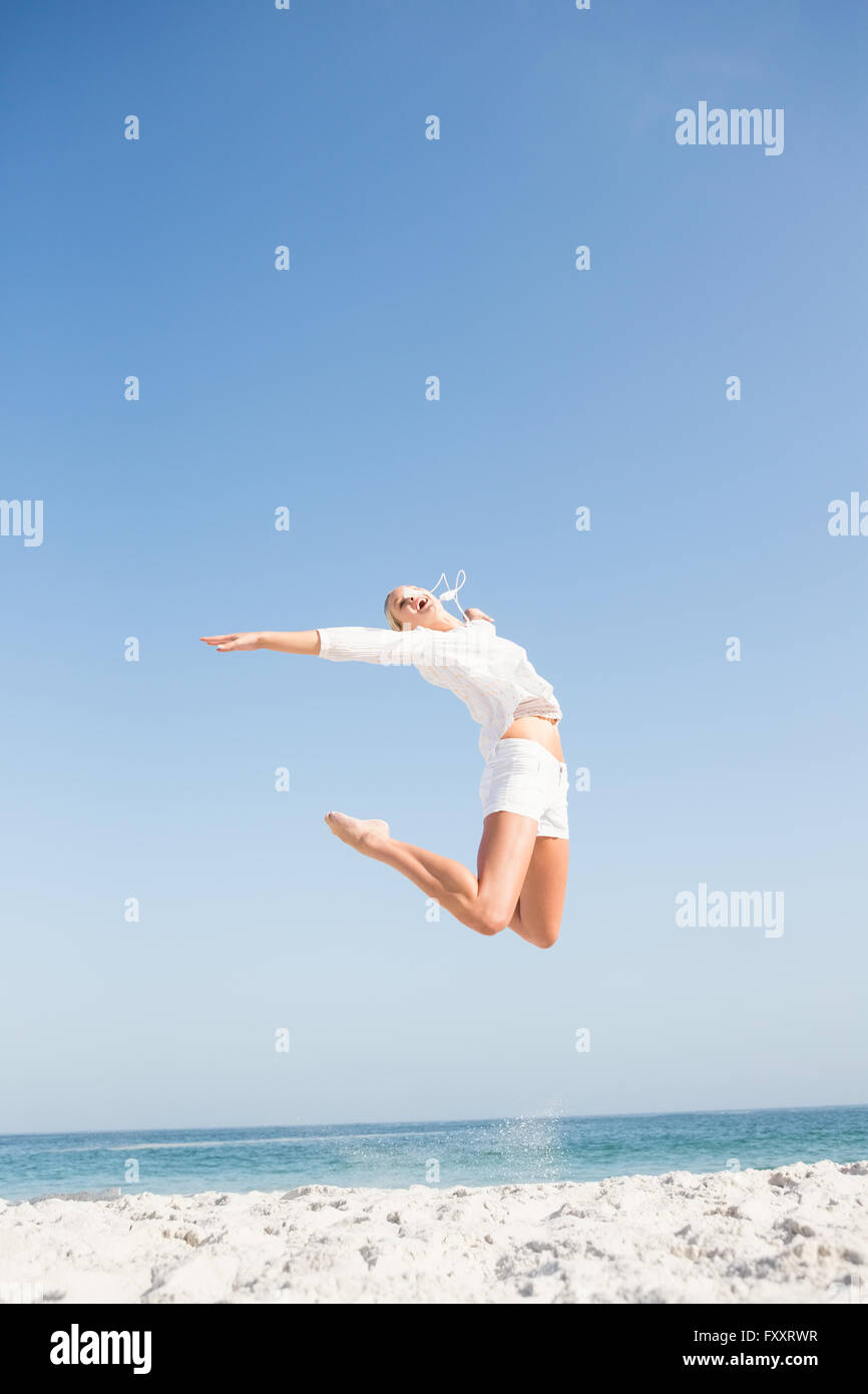 Blonde woman jumping on the beach - Stock Image