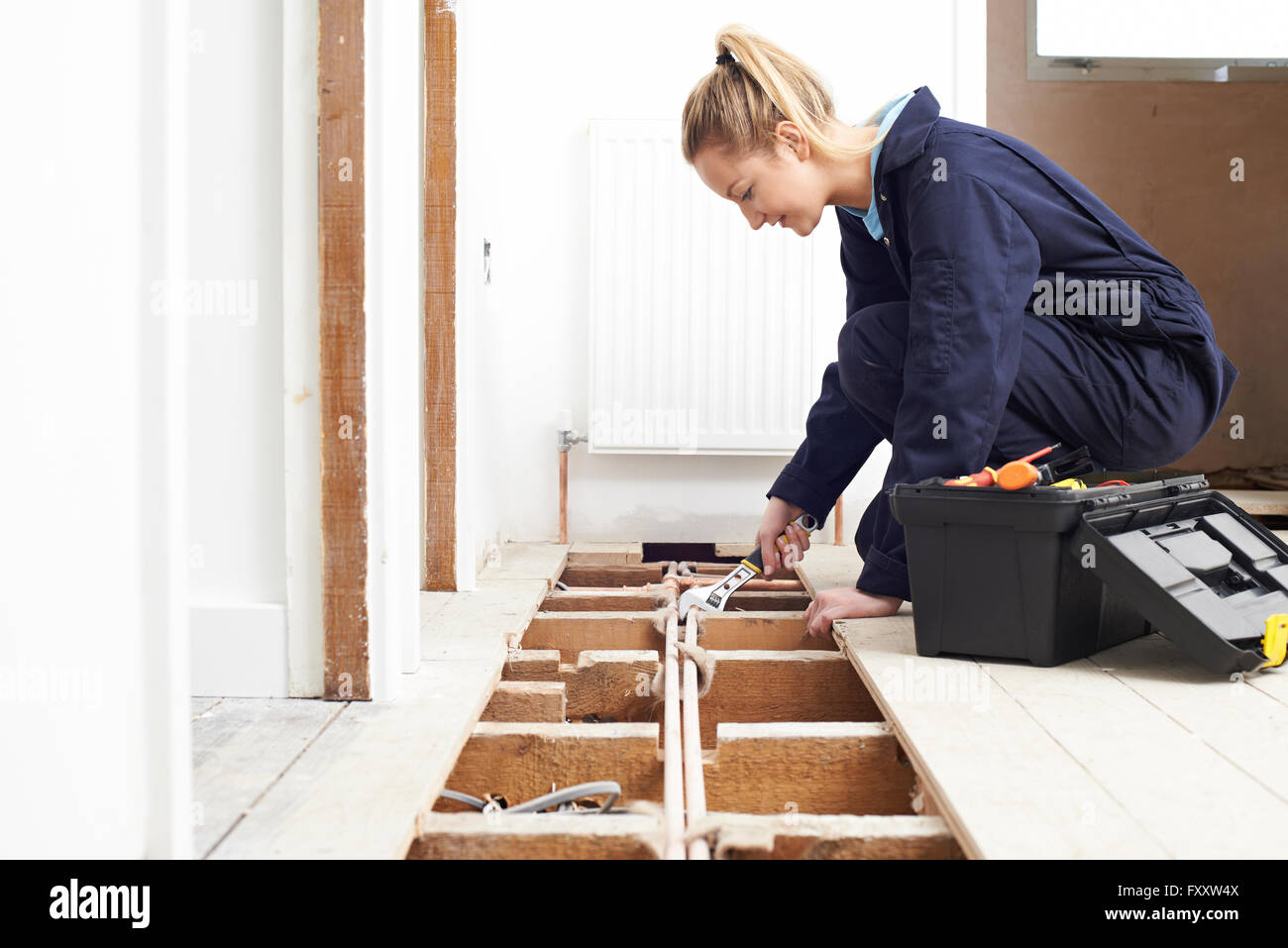 Female Plumber Fitting Central Heating System - Stock Image