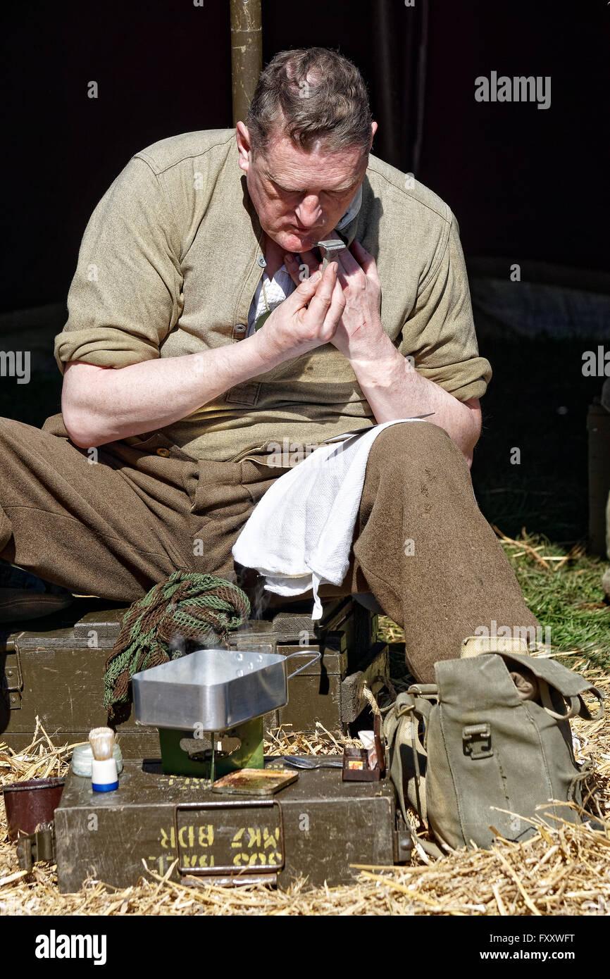 British re-enactor dressed as WW2 soldier shaving - Stock Image