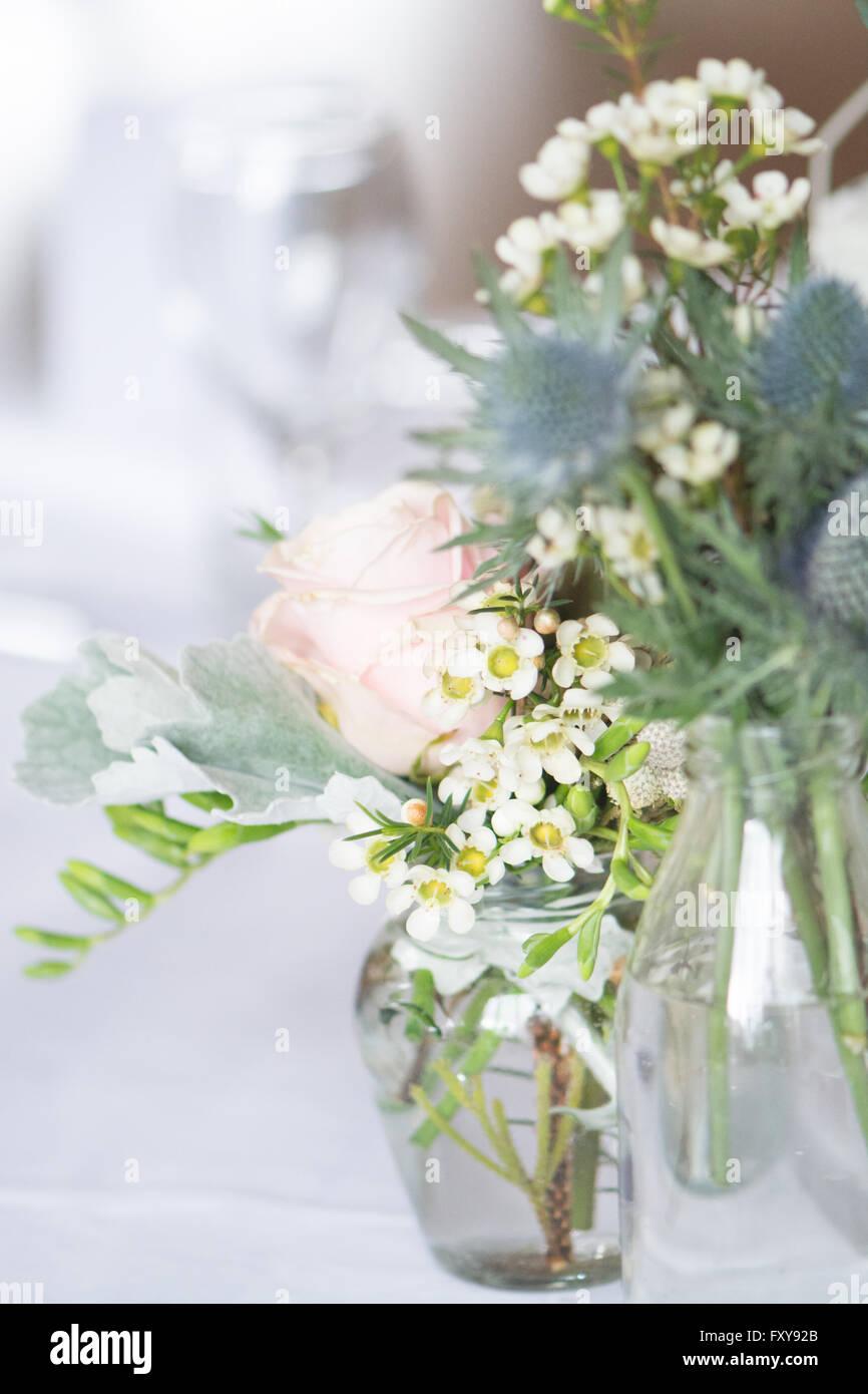 Table set for wedding or event with informal flower arrangements in vintage bottles - Stock Image