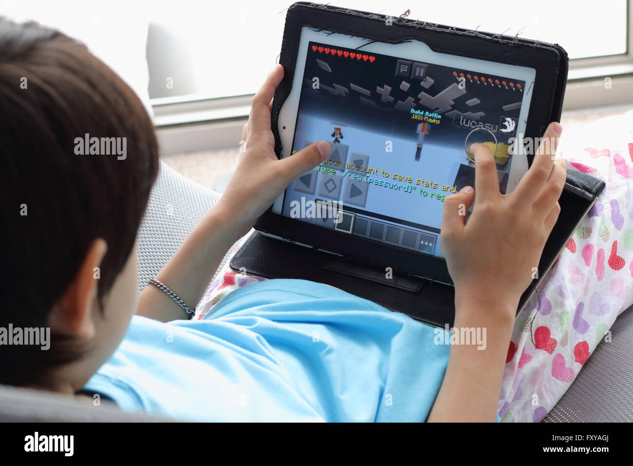 Young child playing Minecraft games on the iPad Stock Photo