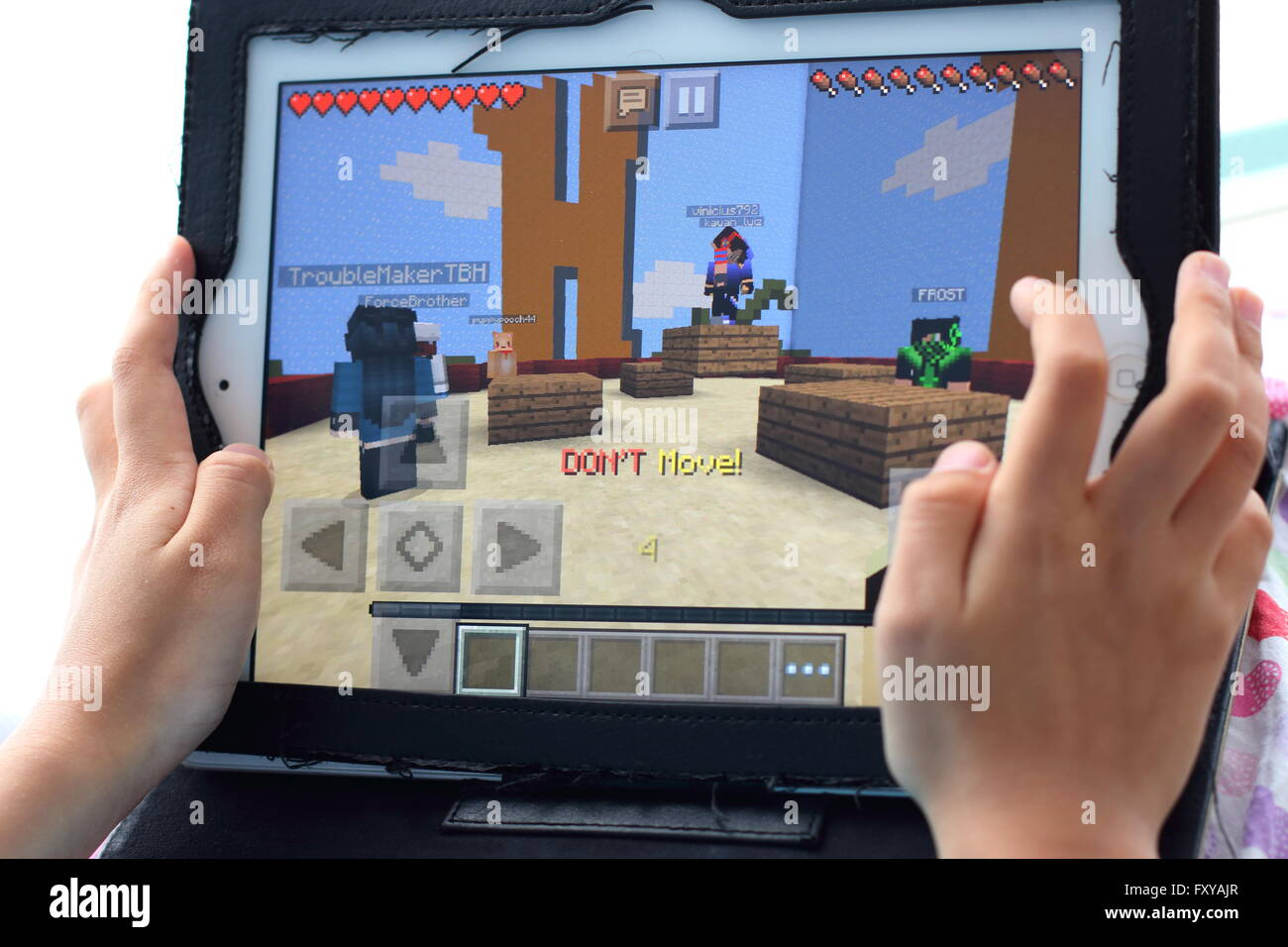 Young child playing Minecraft games on the iPad - Stock Image