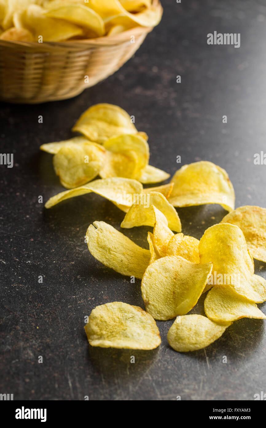 Crispy potato chips on old kitchen table - Stock Image