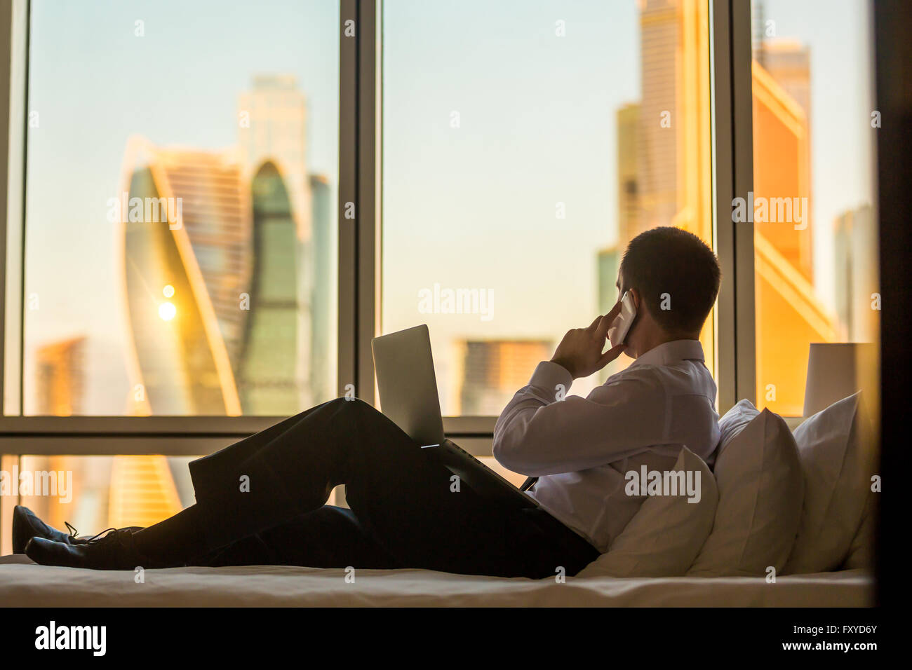Businessperson working at home or in trip. Handsome young businessman sitting on bed with laptop and making call - Stock Image