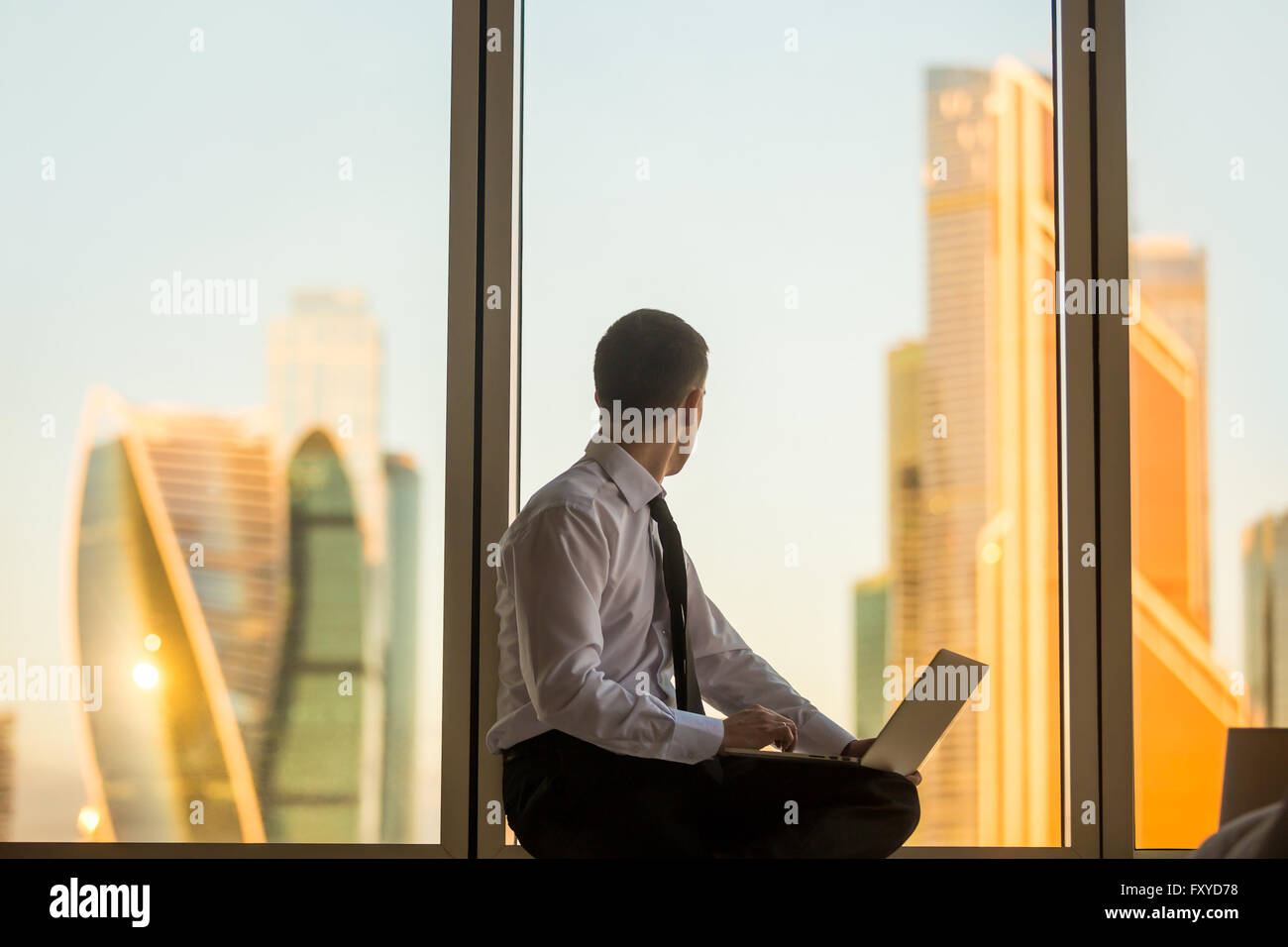Morning in business office. Back view of young man sitting on window with laptop, looking at beautiful dawn city - Stock Image
