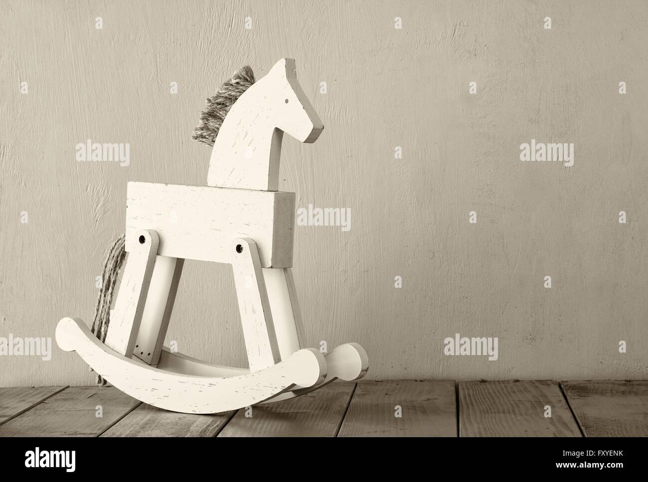 vintage rocking horse on wooden floor. retro filtered image - Stock Image