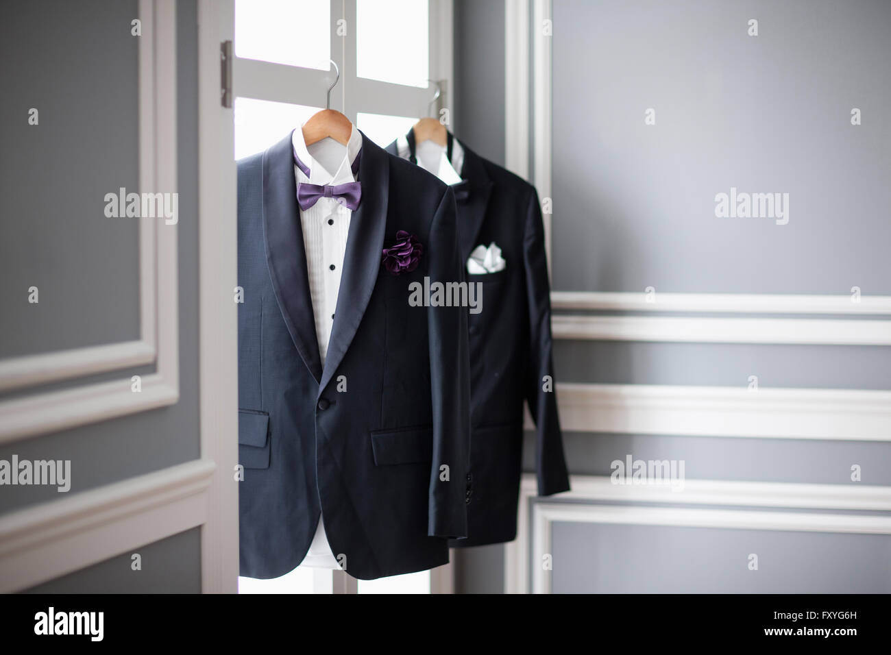 Two sets of tuxedos hung up on windows - Stock Image
